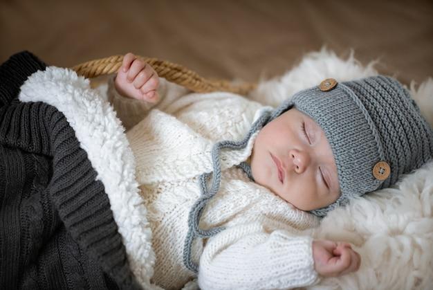 Portrait d'un bébé endormi dans un bonnet tricoté chaud avec un jouet tricoté dans la poignée se bouchent.