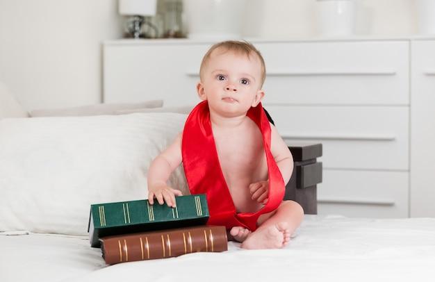 Portrait de bébé garçon de 10 mois en ruban de remise des diplômes en regardant de gros livres