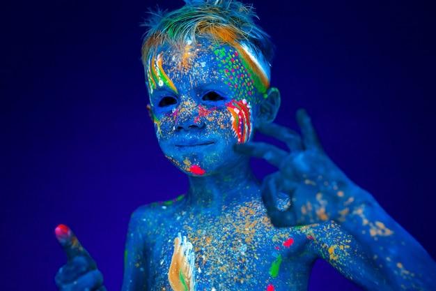 Portrait d'un bébé garçon néon, montre la classe et super à la lumière uv