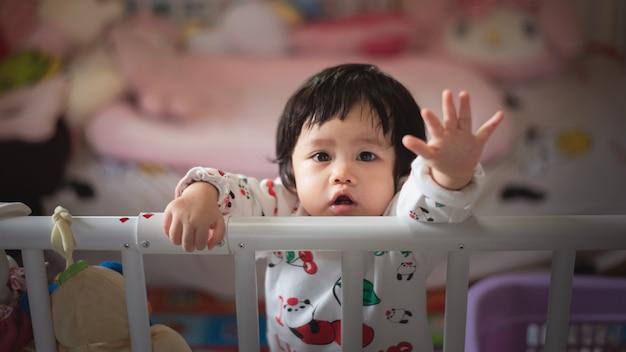 Portrait de bébé mignon dans la barrière de l'enfant