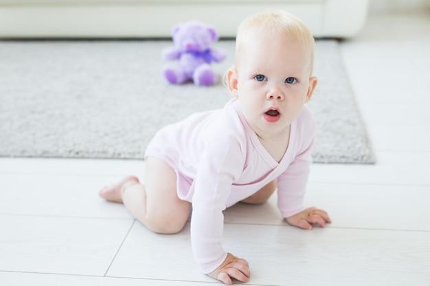 Portrait d'un bébé mignon rampant et riant sur le sol à la maison