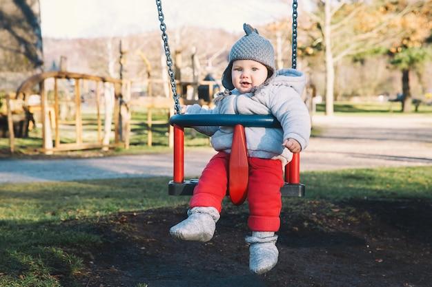 Portrait d'un bébé mignon vêtu de vêtements chauds sur une balançoire à l'aire de jeux par une journée ensoleillée à l'extérieur.