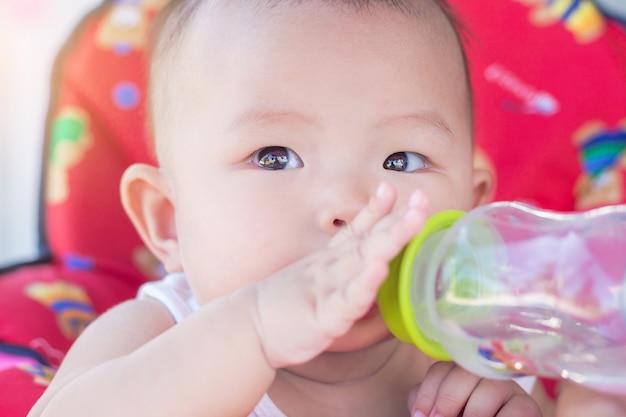 Portrait, de, bébé mignon, sur, voiture jouet, eau potable, de, bouteille