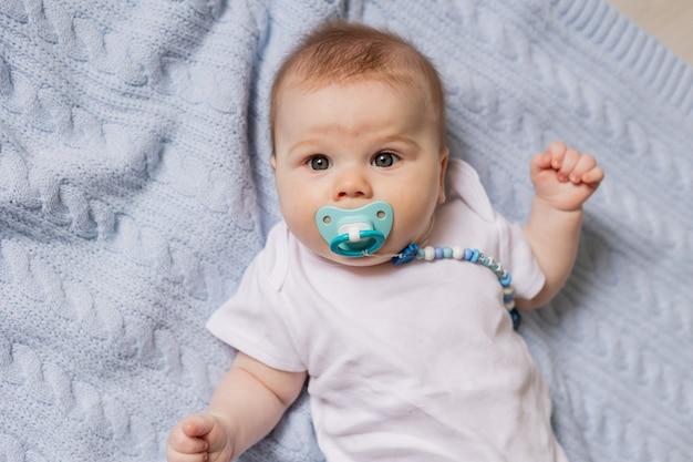Portrait de bébé nouveau-né mignon avec une tétine dans sa bouche allongé sur le dos sur une couverture tricotée bleue