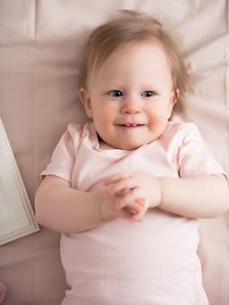 Portrait d'un bébé qui rit heureux, avec une drôle d'expression sur son visage. une belle petite fille aux yeux bleus sourit joyeusement, les premières dents sont visibles.