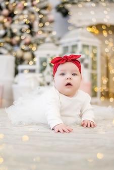 Portrait d'un bébé en robe blanche avec paille rouge, chaussons. le fond d'un arbre de noël de luxe