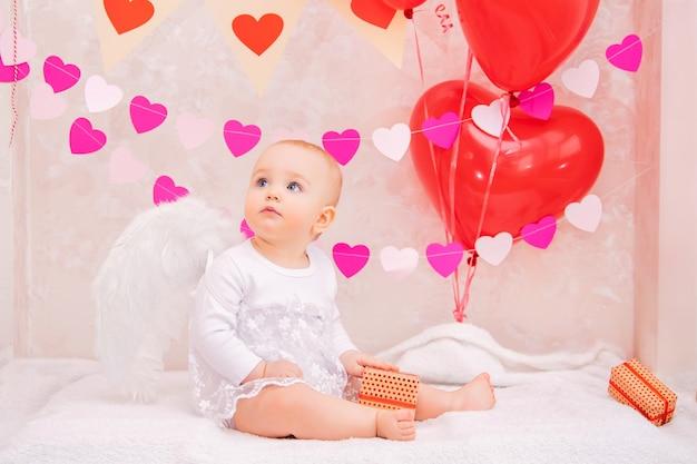 Portrait d'un bébé surpris avec des ailes de plumes blanches, avec des cadeaux dans des boîtes, symboles de la saint-valentin.