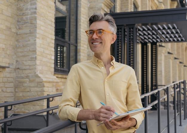 Portrait de bel écrivain prenant des notes, debout dans la rue, souriant