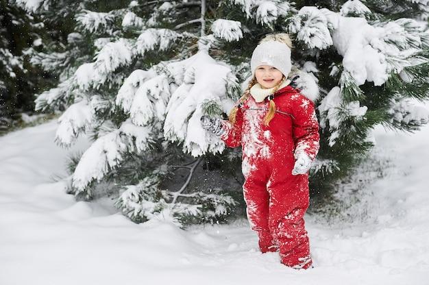 Portrait d'un bel enfant caucasien dans une salopette rouge sur fond d'arbres de noël couverts de neige