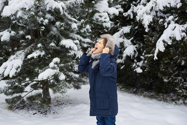 Portrait d'un bel enfant caucasien sur fond d'arbres de noël couverts de neige
