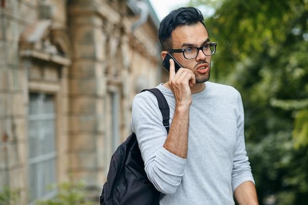 Portrait de bel étudiant de sexe masculin à l'extérieur sur le campus universitaire et parler au téléphone mobile, copiez l'espace