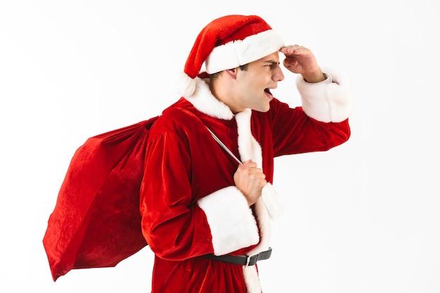 Portrait de bel homme 30 s en costume de père noël et chapeau rouge marchant avec sac-cadeau sur l'épaule