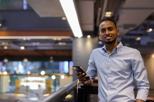 Portrait d'un bel homme d'affaires africain noir à l'intérieur d'un centre commercial souriant et tenant un plan horizontal de téléphone portable