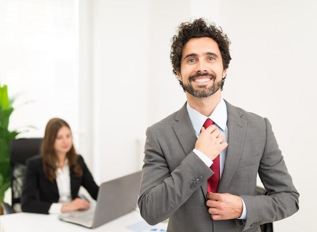 Portrait d'un bel homme d'affaires ajustant sa cravate