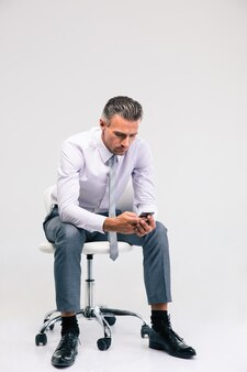 Portrait d'un bel homme d'affaires assis sur la chaise de bureau et utilisant un smartphone isolé