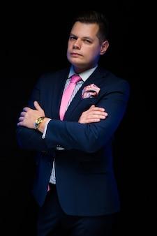 Portrait de bel homme d'affaires avec les bras croisés sur fond noir