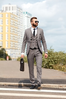 Portrait de bel homme d'affaires caucasien avec sac à la réunion d'affaires