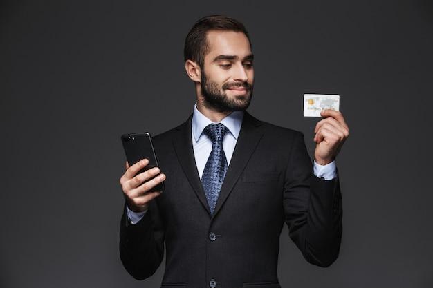 Portrait d'un bel homme d'affaires confiant portant costume isolé, à l'aide de téléphone mobile, montrant une carte de crédit en plastique