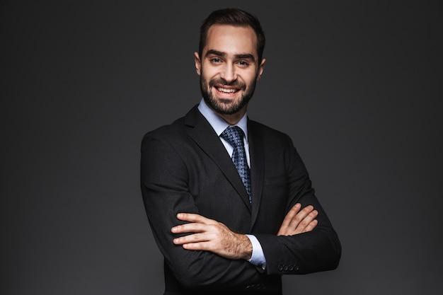 Portrait d'un bel homme d'affaires confiant portant costume isolé, bras croisés