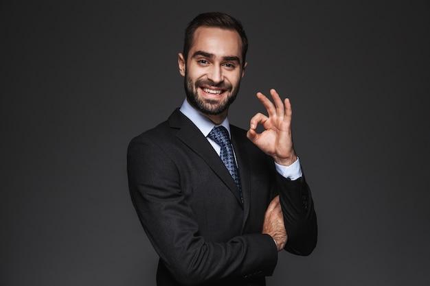 Portrait d'un bel homme d'affaires confiant portant costume isolé, geste ok