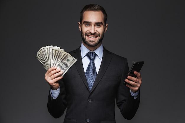 Portrait d'un bel homme d'affaires confiant portant costume isolé, montrant des billets d'argent, à l'aide de téléphone mobile