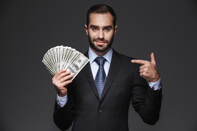 Portrait d'un bel homme d'affaires confiant portant costume isolé, montrant des billets d'argent
