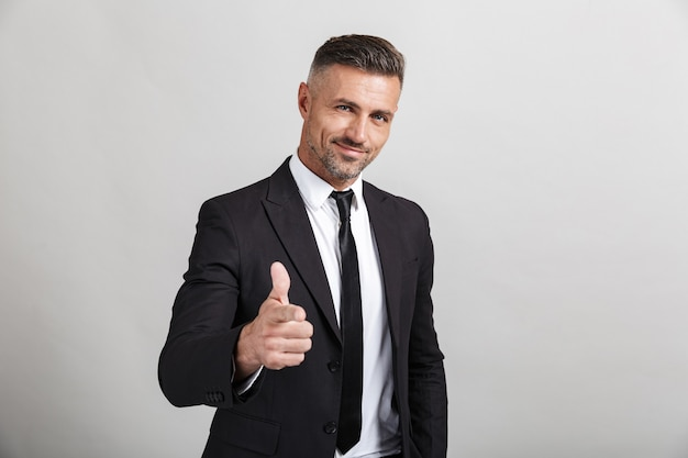 Portrait d'un bel homme d'affaires confiant portant un costume isolé, montrant les pouces vers le haut