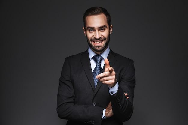 Portrait d'un bel homme d'affaires confiant portant costume isolé, pointant le doigt à l'avant
