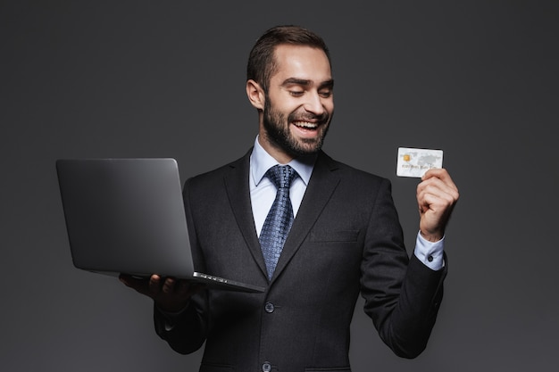 Portrait d'un bel homme d'affaires confiant portant costume isolé, tenant un ordinateur portable, montrant la carte de crédit