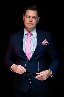 Portrait de bel homme d'affaires confiant tenant des lunettes de soleil dans ses mains sur un fond noir avec les mains dans les poches