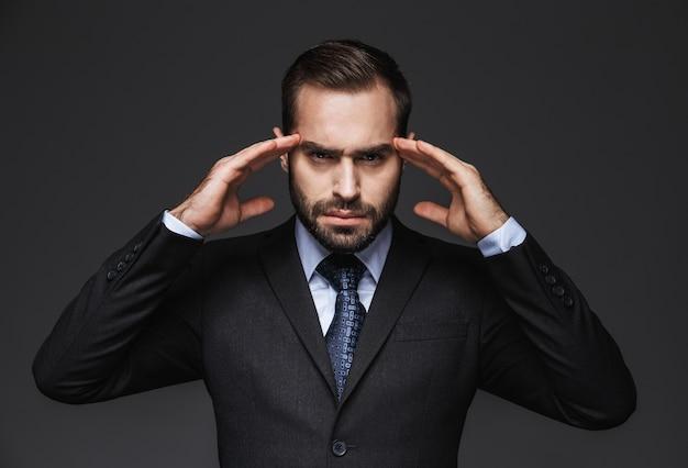 Portrait d'un bel homme d'affaires fou portant costume isolé, ayant mal à la tête