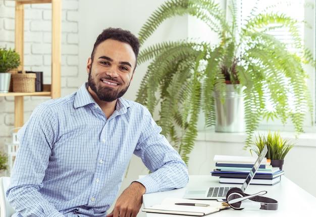 Portrait de bel homme d'affaires jeune noir africain travaillant sur ordinateur portable au bureau