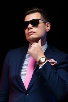 Portrait de bel homme d'affaires en lunettes de soleil tenant la main près de barbe sur fond noir
