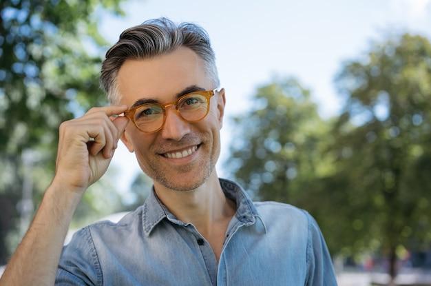 Portrait de bel homme d'affaires mature portant des lunettes, regardant la caméra, souriant