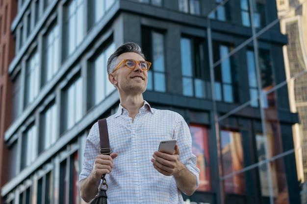 Portrait de bel homme d'affaires mature tenant le sac de messager, portant des lunettes élégantes