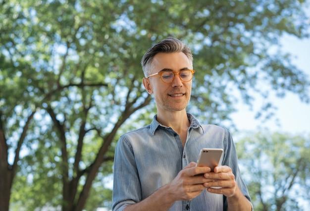Portrait de bel homme d'affaires mature tenant un téléphone mobile