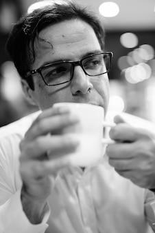 Portrait d'un bel homme d'affaires persan relaxant au café en noir et blanc