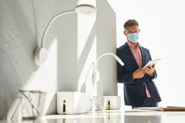 Portrait de bel homme d'affaires portant un masque et tout en s'appuyant sur le mur dans un bureau blanc minimal, espace copie