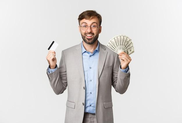 Portrait de bel homme d'affaires riche et lunettes, shopping avec carte de crédit et argent