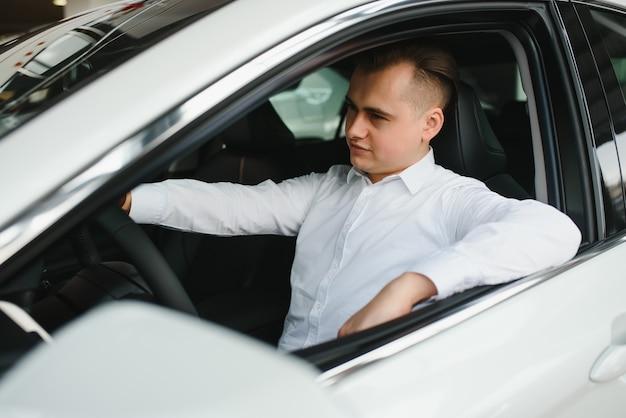 Portrait d'un bel homme d'affaires souriant au volant de sa voiture