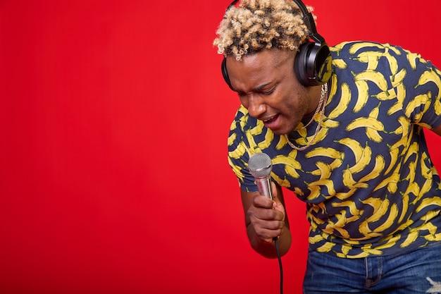 Portrait d'un bel homme africain positif avec un microphone et des écouteurs sur la tête