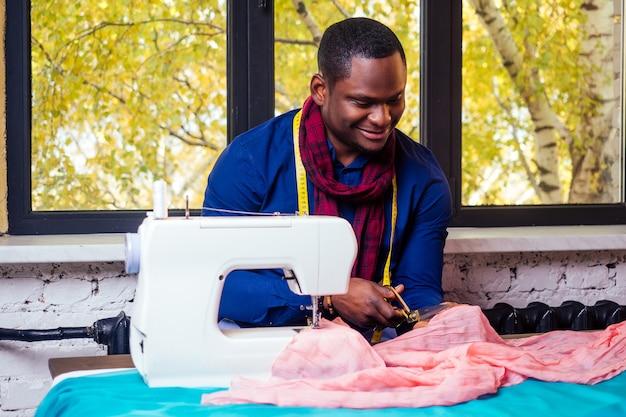 Portrait d'un bel homme africain souriant couturière avec machine à coudre. afro-américain designer élégant travaillant dans un mannequin d'atelier sur mesure, ruban à mesurer de table dans la chambre contre la fenêtre d'automne