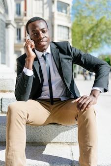 Portrait d'un bel homme africain souriant lorsqu'il utilise son téléphone portable dans la rue.