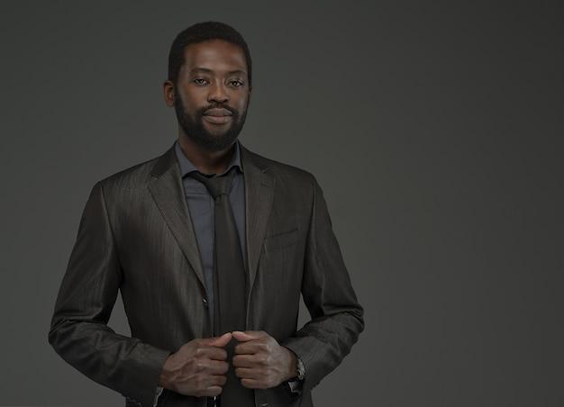 Portrait de bel homme afro-américain barbu d'âge moyen avec un sourire doux sur le visage.homme vêtu d'une chemise de couleur charbon, costume gris et cravate pose