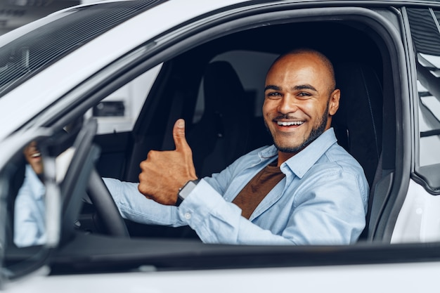 Portrait d'un bel homme afro-américain heureux assis dans sa voiture nouvellement achetée