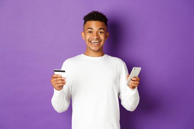 Portrait de bel homme afro-américain, souriant et à la recherche d'excité lors de vos achats en ligne