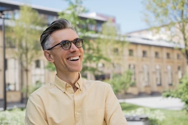 Portrait de bel homme d'âge mûr portant des lunettes de soleil, marchant dans la rue, riant.