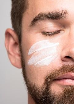Portrait de bel homme à l'aide de gros plan de crème pour le visage
