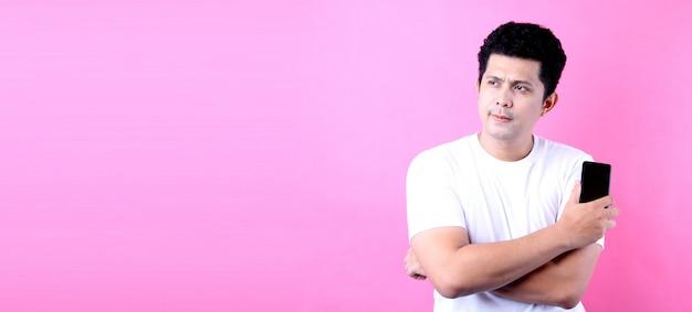 Portrait de bel homme asiatique au look rêveur, pensant tout en tenant le smartphone, sur le mur rose.