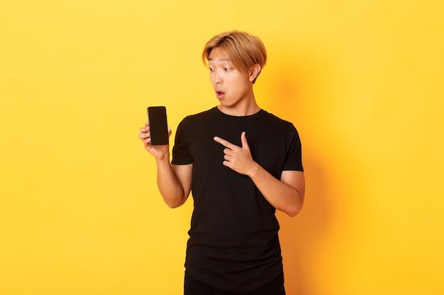 Portrait de bel homme asiatique montrant quelque chose sur l'écran du smartphone